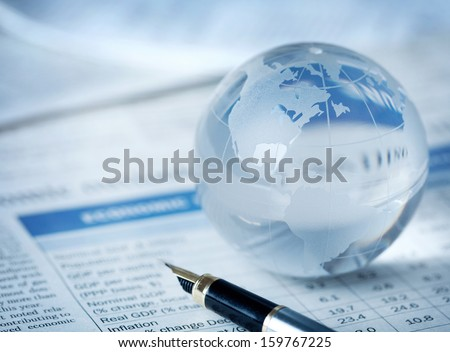 Glass globe on financial report  - stock photo