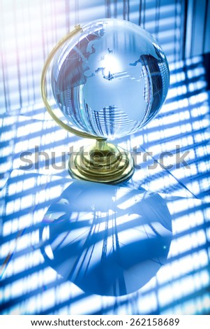 Glass globe on paper background, shadow of blind. Lens flare. Business concept.  - stock photo