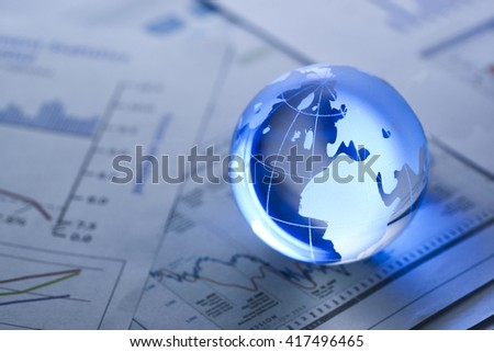 Glass globe on  stock market chart . shot with very shallow depth of field. blue tone