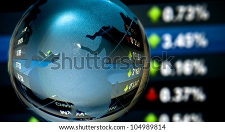 Glass globe over stock data on computer screen