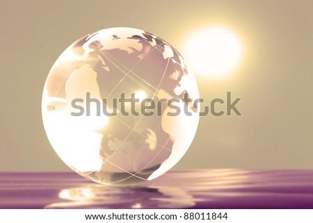 Glass globe with bright highlights on a yellow background - stock photo
