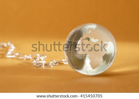 Glass globe with steel chain - stock photo