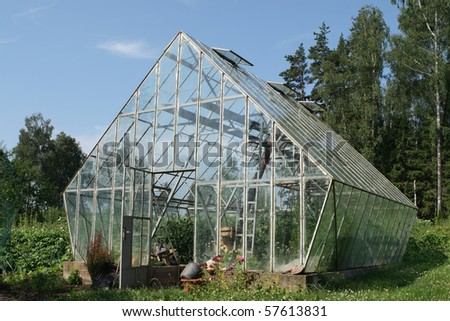 Glass greenhouse in countryside. - stock photo