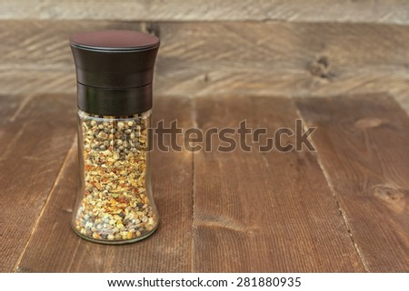 Glass grinder for spices on wooden background. Ingredients for masala, Indian spice mix - stock photo
