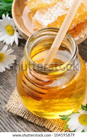Glass honey pot and comb with daisies - stock photo