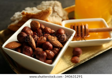 Glass jar and bowl with honey and nuts on gray background