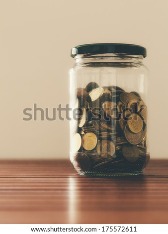 Glass jar containing coins on the wooden table - stock photo