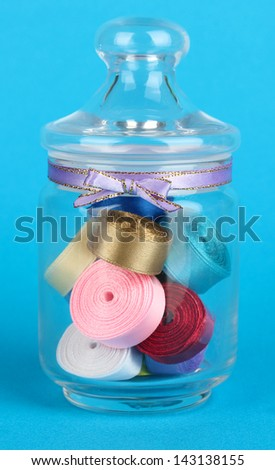 Glass jar containing various colored ribbons on blue background - stock photo