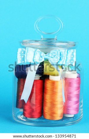 Glass jar containing various colored thread on blue background - stock photo