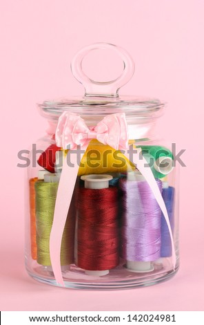 Glass jar containing various colored thread on pink background - stock photo