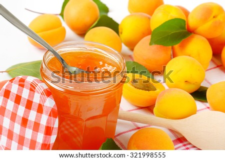 glass jar full of apricot jam with immersed teaspoon