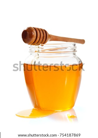 glass jar full of honey and dipper isolated on white background