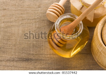 glass jar full of honey and stick on wood background - stock photo