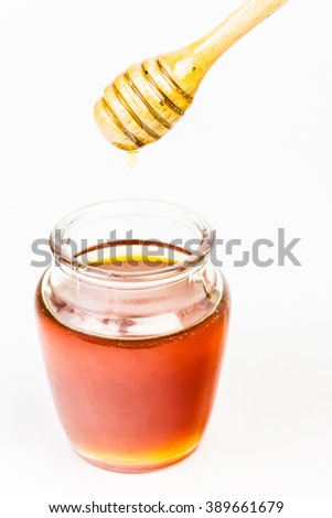 Glass jar full of honey wooden honey dipper on white background - stock photo