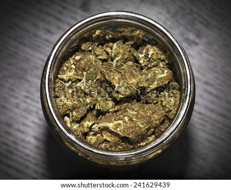Glass jar full of marijuana on wooden black table  - stock photo