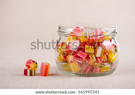 Glass jar full of tutti-frutti sugar candies mix and three candies lying out of jar on material, colourful hand made sweets, horizontal orientation, studio shot, front view. - stock photo