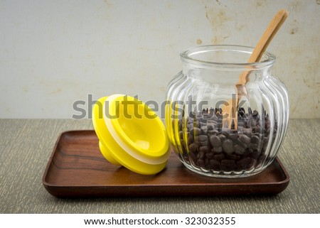 Glass jar of coffee on the tray wood