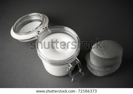 Glass jar of cosmetic cream and stack of massage stones on dark grey background.