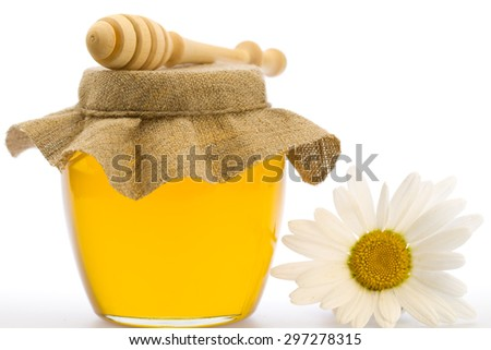glass jar of fresh honey with drizzler isolated on white background - stock photo