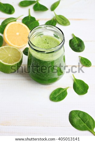 Glass jar of fresh summery drink green smoothie, spinach leaves, lime fruit. Vertical. - stock photo