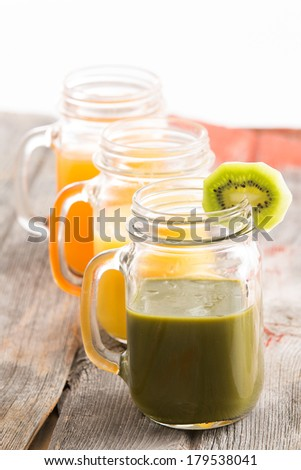 Glass jar of healthy kiwifruit smoothie garnished with a slice of fresh kiwi together with jars of mango and orange juice in a receding row on an old wooden table - stock photo