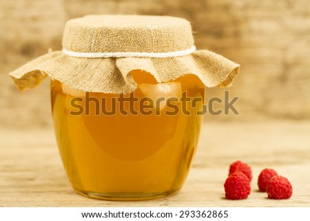 glass jar of honey closed jute cloth and raspberries on wooden background - stock photo