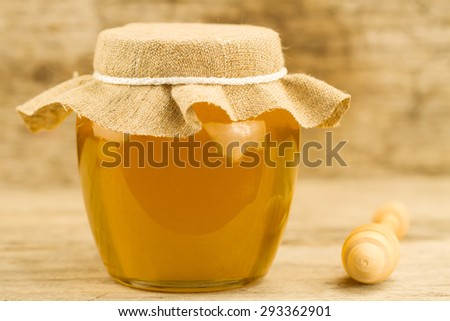 glass jar of honey closed jute cloth drizzler on wooden background - stock photo