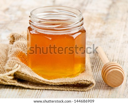 Glass jar of honey with wooden stick