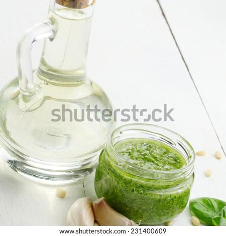 Glass jar of pesto sauce on white kitchen table - stock photo