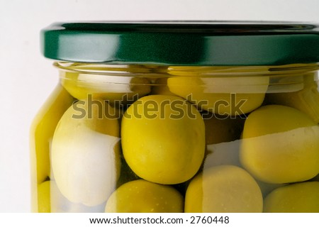 Glass jar of preserved olives (vertical closeup)