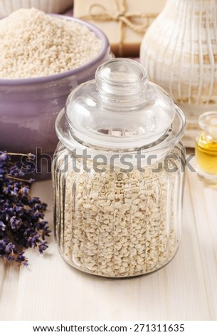 Glass jar of sea salt on white wooden table, lavender flowers in the background - stock photo