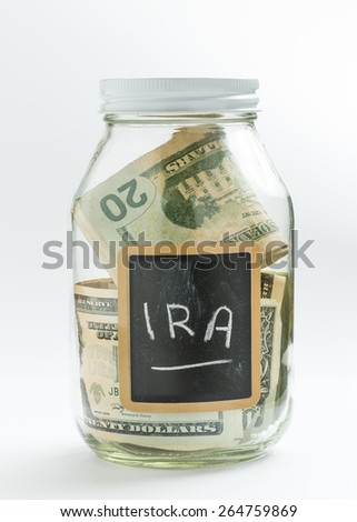 Glass jar on white background with black chalk label or panel and used for saving of US dollar bills for IRA and retirement - stock photo