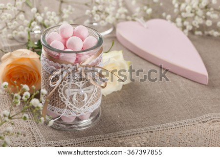 Glass jar with candy, Valentines heart and roses on the tablecloth - stock photo
