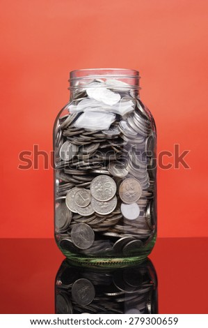 Glass jar with coin isolated on red background                              - stock photo