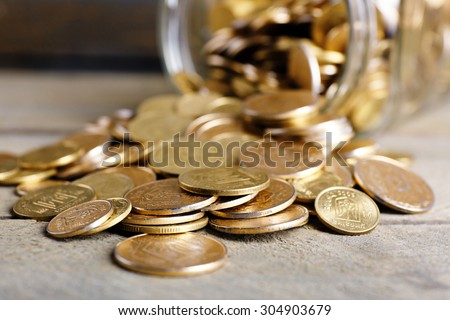 Glass jar with coins on wooden table, closeup