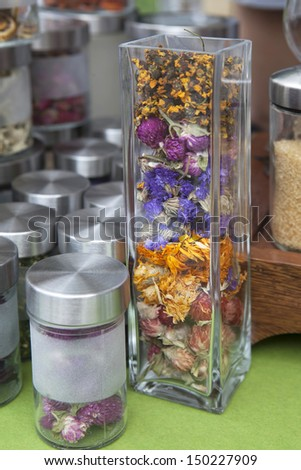 glass jar with colorful flower petals - stock photo
