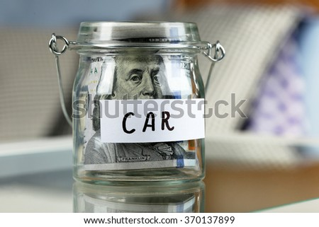 Glass jar with dollar banknotes for car on a table - stock photo