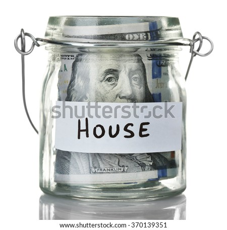 Glass jar with dollar banknotes for house, isolated on white - stock photo