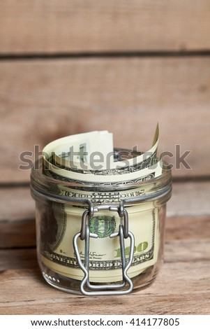 Glass jar with dollar bills