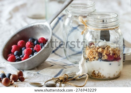 Glass jar with homemade granola and yogurt served with nuts, raspberries and blackberries in vintage colander over white textile in day light. - stock photo