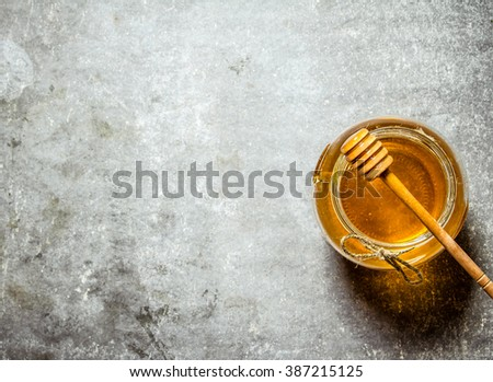Glass jar with honey . On a stone background. - stock photo
