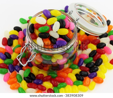 Glass Jar with Lid and Metal Clasp Open and Overflowing with Jelly Beans - stock photo