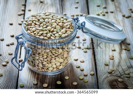 glass jar with organic green lentils on wooden background - stock photo