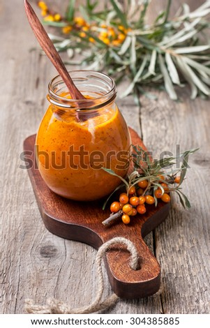 glass jar with sea buckthorn jam on a wooden background - stock photo