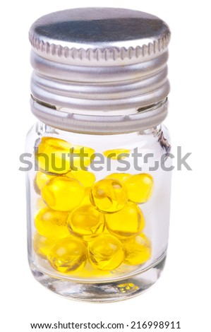 Glass jar with yellow capsules of fish oil. Close-up with shallow DOF. Isolate on white background. - stock photo