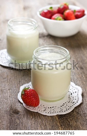 glass jar with yogurt on a wooden background
