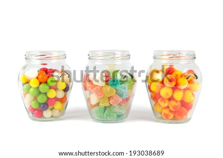Glass jars filled with different colorful candies  - stock photo