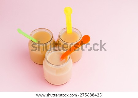 Glass jars of baby puree with colorful spoons on pink background with copy space - stock photo