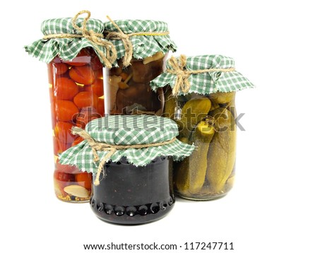 Glass jars of preserved mushrooms, tomatoes, pickled cucumbers and jam on a white background