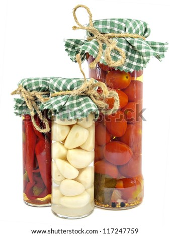 Glass jars of preserved tomatoes, garlic and red hot peppers on a white background - stock photo